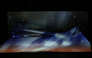 Set against a black and white starry sky, the ramp glows with white and grey projections of rock. The edges of the ramp are highlihted in white.