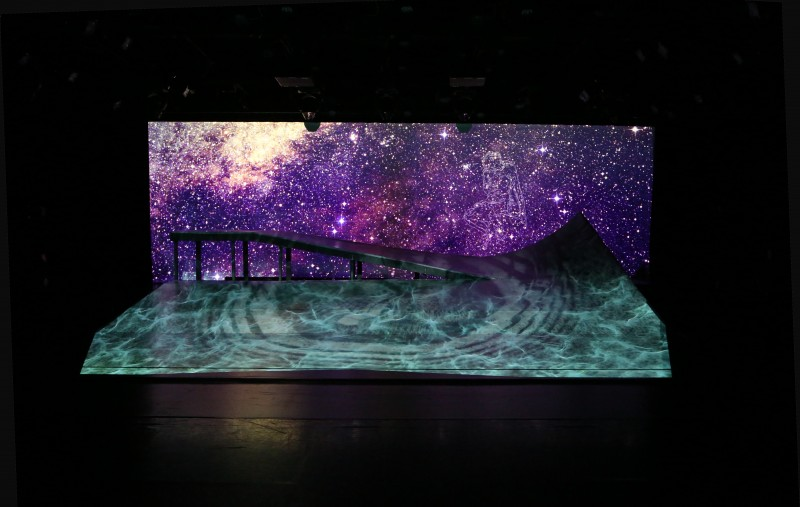 A brilliant purple starry sky filled with constellations is contrasted with aquamarine water waves that also looks like flames projected on to the ramp by video. You can see a shadow of the downhill slopes and uphill peaks that embody the title of the piece DESCENT.