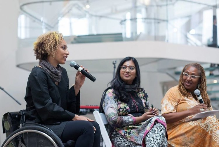 Alice in the Queens Museum atrium holding a microphone and joined by panelist Shahana Hanif and moderator Lisa Cortez. Photo courtesy of Brian Tate.