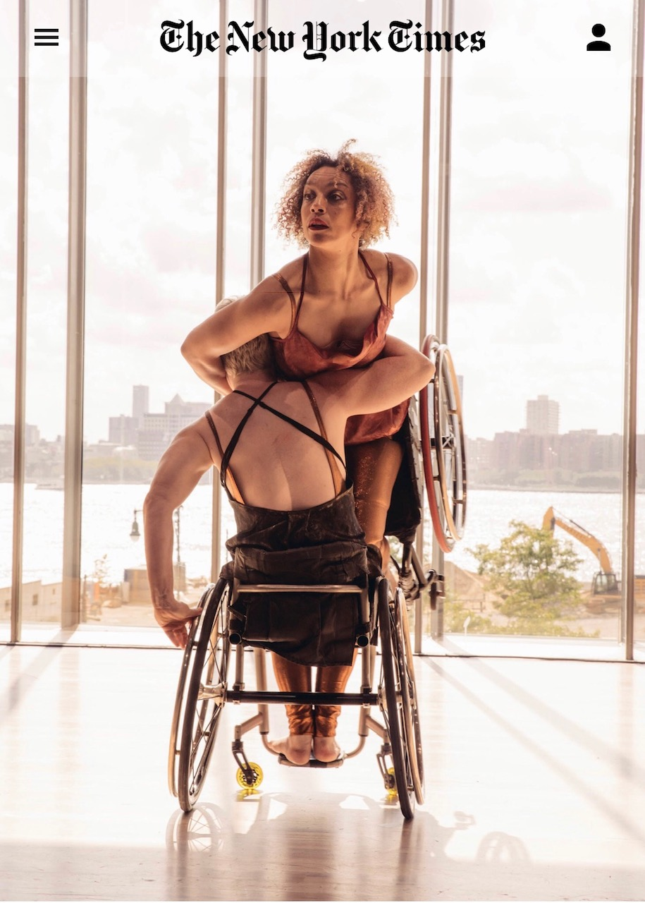 Alice Sheppard kneels on the lap of Laurel Lawson with arms wrapped around Laurel's head. They are both strapped into their wheelchairs and the background is recognizably the open windows of The Whitney Museum when looking at the Hudson River. Sculpted backs and arms and skin are spiraled with Alice's open face inhaling in mid-spin and Laurel's left fingertips on her silver rim. Photo by Michael Kirby Smith.