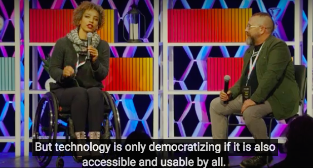 Alice Sheppard on a conference stage with Charles Baldwin. Text read: Technology is only democratizing if it is accessible and usable by all.