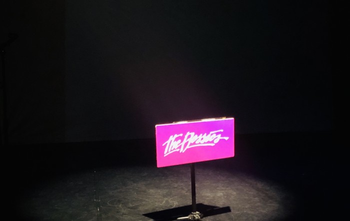 Dark stage with a spotlight on a music stand at the height for a wheelchair and a hot pink sign that reads 'The Bessies'
