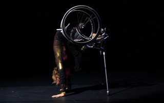 Alice balances on her hands, arms straight, and on a pair of silver crutches, lifting her lower body and wheelchair high. Alice's head is tucked and her short curly hair peeks out from behind her strong arms. She is wearing a shimmery gold bodysuit. She is set against a black background and light reflects off her costume, chair, and crutches.