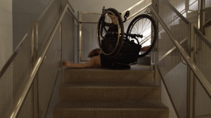 Dressed in black, Alice in her wheelchair attempts to climb the sparkling metal and concrete staircase.  She lies on her back, head hidden , body caught between the railings, step and landing.