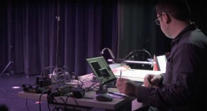 Alexander Reben, a white man with dark hair and glasses, focuses on the laptop in front of him.  In background are a black curtain and a dance floor and a pile of wild cables.